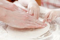 Mother and child hands prepares the dough with flour for bread or pizza. Bakery background. Mother and child hands prepares the dough with flour, rolling pin Stock Image