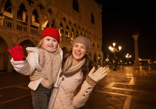 Mother and child handwaving on Piazza San Marco in the evening Stock Photo