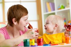 Mother and child have fun with paints Royalty Free Stock Photo