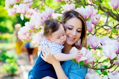 Mother and child have a lasure in Magnolia garden Royalty Free Stock Image