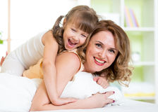 Mother and child having fun in bed Royalty Free Stock Photos
