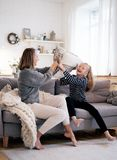 Mother and child having fun in pillow fight on sofa bed in bedroom. Happy family spending time together royalty free stock photos