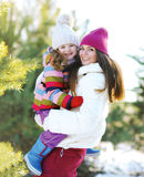Mother and child having fun playing outdoors in the winter Stock Photo