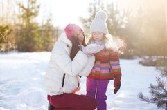 Mother and child having fun in sunny winter Royalty Free Stock Image
