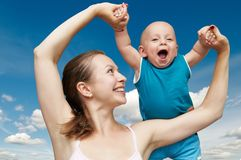 Mother and child in her hands. Happy mother holding the laughing child in her hands Royalty Free Stock Image