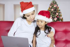 Mother and child hold a credit card. Asian women holding a credit card while using a computer laptop with her daughter and sitting on the couch Stock Photo