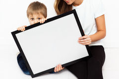 Mother with child holding a frame. Royalty Free Stock Image