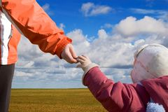 Mother and child holding hands. Mother and child hoding each other hand  under blue skies Royalty Free Stock Photos