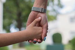Mother and a child holding hands. On blurred background Stock Image