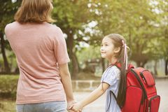 Mother and child holding hands going to school royalty free stock photos