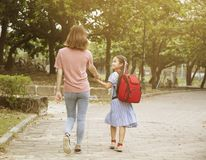 Mother and child holding hands going to school stock photos