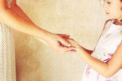 Mother and child holding hands over pink textured background Royalty Free Stock Photos