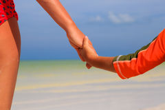 Mother and child holding hands on sea beach Stock Photography