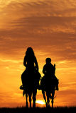 Mother and child on horse at sunset Stock Image
