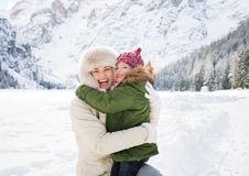 Mother and child hugging outdoors in front of snowy mountains Royalty Free Stock Photo