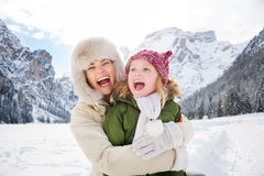 Mother and child hugging outdoors in front of snowy mountains. Winter outdoors can be fairytale-maker for children or even adults. Happy mother and child hugging royalty free stock image