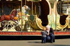Mother and Child. An image of a mother and child conversation in front of a carousel in Montmarte, France.  This is a typical type of amusement found in the Royalty Free Stock Photos