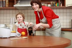 Mother and child in the kitchen. Woman and boy preparing food in domestic kitchen with food processor Royalty Free Stock Photo