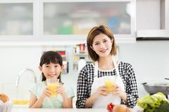 Mother and child in kitchen drinking juice Royalty Free Stock Images