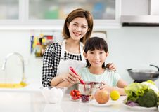 Mother and child in kitchen preparing cookies Stock Photos
