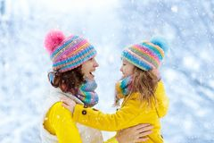 Mother and child in knitted winter hats in snow stock images