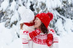 Mother and child in knitted winter hats in snow stock photo