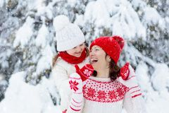 Mother and child in knitted winter hats in snow stock photography