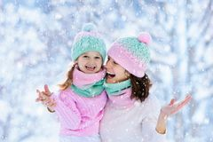 Mother and child in knitted winter hats in snow. royalty free stock photo