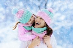 Mother and child in knitted winter hats in snow. stock photos