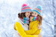 Mother and child in knitted winter hats in snow stock photos