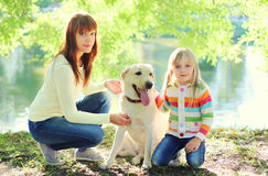Mother and child with Labrador retriever dog and in summer Royalty Free Stock Photos