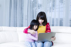 Mother and child with laptop on couch Royalty Free Stock Photography
