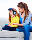 Mother with child learning home work. With tab pc Royalty Free Stock Photography