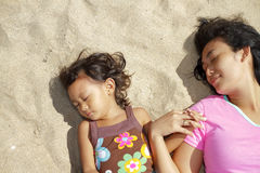 Mother and child lie down on the beach sand Stock Image