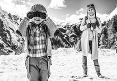 Mother and child looking into camera through binoculars. Winter on higher level of fun. modern mother and child travellers in the front of mountain scenery in stock photo