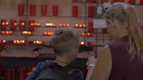 Mother and child looking at candles in church. Mother and son looking at numerous red candles in St. Lawrence Church, Rotterdam. Woman taking shot on smart phone stock footage