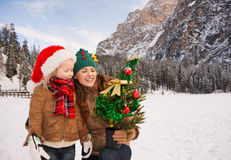 Mother and child looking on Christmas tree in front of mountains Stock Photo