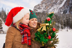 Mother and child looking on Christmas tree in front of mountains Royalty Free Stock Image