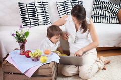 Mother and child, looking at a computer, eating fruits Royalty Free Stock Photos