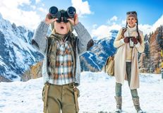 Mother and child looking into distance through binoculars. Winter on higher level of fun. modern mother and child travellers in the front of mountain scenery in royalty free stock photo