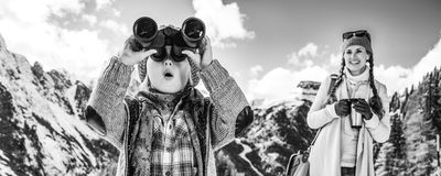 Mother and child looking into distance through binoculars. Winter on higher level of fun. modern mother and child travellers in the front of mountain scenery in stock images