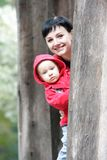 Mother and child looking out from tree Stock Photography
