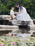 Mother and Child by lotus pond. A Chinese mother and her young son explore the natural world beside a pond full of lotus flowers and lily pads Royalty Free Stock Photography