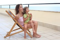 Mother with child in lounge on veranda Royalty Free Stock Photos