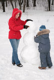 Mother and child make snowman. Mother and child (boy) make snowman Royalty Free Stock Images