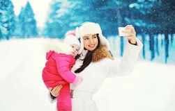 Mother with child makes photo self-portrait on smartphone in winter Royalty Free Stock Images