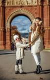Mother and child near Arc de Triomf in Barcelona handwaving. In Barcelona for a perfect winter. Full length portrait of happy young mother and child near Arc de Stock Photography
