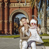 Mother and child near Arc de Triomf in Barcelona handwaving. In Barcelona for a perfect winter. Portrait of happy young mother and child near Arc de Triomf in Royalty Free Stock Images