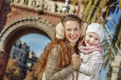 Mother and child near Arc de Triomf in Barcelona hugging. In Barcelona for a perfect winter. Portrait of smiling trendy mother and child near Arc de Triomf in Royalty Free Stock Image