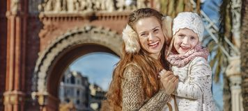 Mother and child near Arc de Triomf in Barcelona hugging. In Barcelona for a perfect winter. Portrait of smiling trendy mother and child near Arc de Triomf in Stock Images